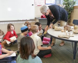 Linda Cunningham, a jeweler and grandparent of student Corinne Hyman (age 8) shows students her collection of fossils including ammonites, petrified wood, brachiopods and crinoids.