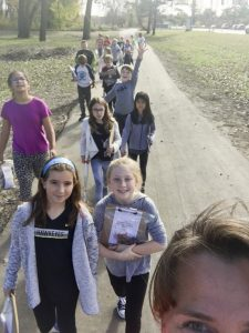 Teacher takes selfie with students walking on trail.