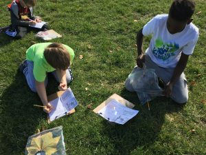 Two students kneel in the grass writing in notebooks.