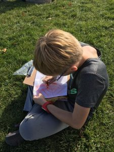 A student sits in the grass writing in a notebook.