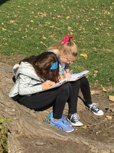 Two students sit in the grass under a tree writing in notebooks.