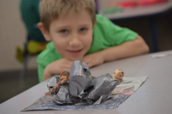 Students display their clay animals in paper habitats.